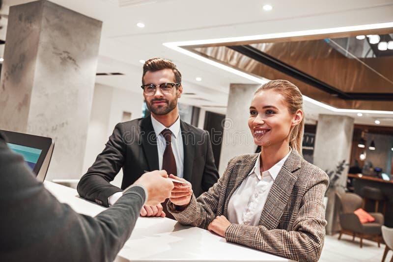 Ζεύγος σε ένα επαγγελματικό ταξίδι που κάνει την είσοδο στο ξενοδοχείο στοκ φωτογραφία με δικαίωμα ελεύθερης χρήσης