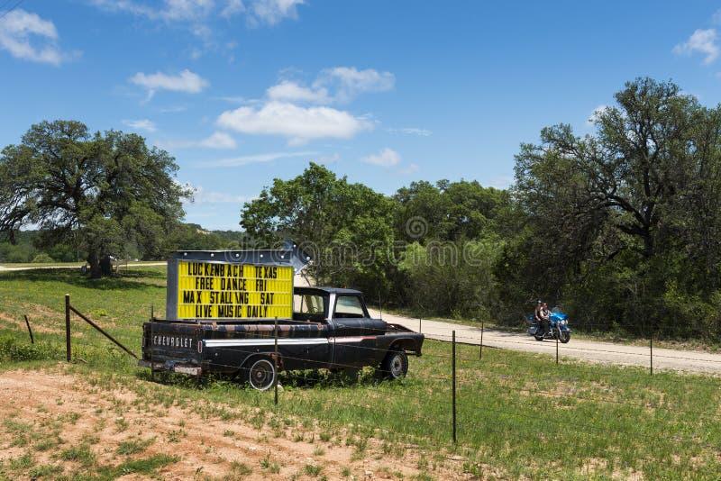 Ζεύγος σε μια μοτοσικλέτα που περνά από ένα φορτηγό με ένα σημάδι για ένα γεγονός μουσικής σε Luckenback, Τέξας στοκ εικόνες