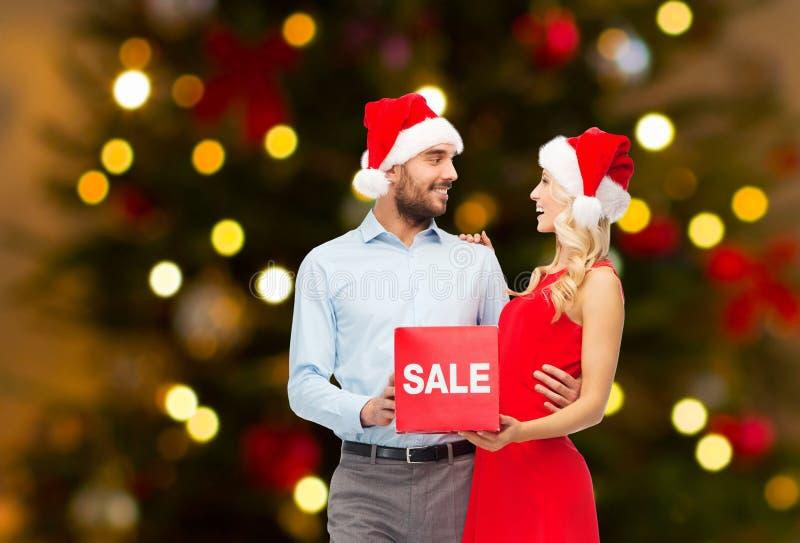 Ζεύγος στα καπέλα santa με το σημάδι πώλησης στα Χριστούγεννα στοκ φωτογραφία με δικαίωμα ελεύθερης χρήσης