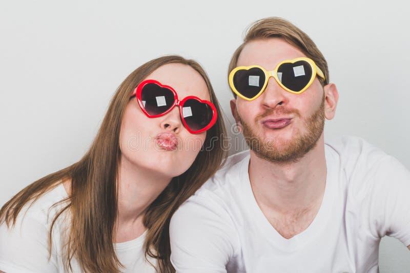 Ζεύγος στα καρδιά-διαμορφωμένα γυαλιά ηλίου στοκ φωτογραφίες