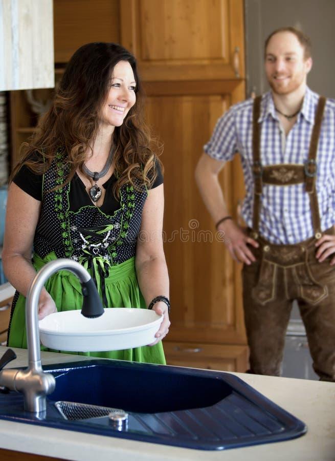 Ζεύγος στα παραδοσιακά βαυαρικά ενδύματα που στέκονται στην κουζίνα στοκ εικόνα