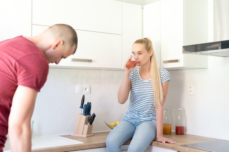 Ζεύγος στην κουζίνα Γυναίκα που πίνει τον υγιή σπιτικό χυμό φρούτων Να κάνει δίαιτα και detox έννοια στοκ φωτογραφία