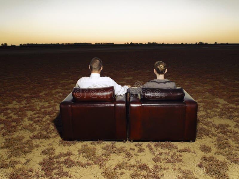 Ζεύγος στις πολυθρόνες που προσέχει το ηλιοβασίλεμα στην ανοικτή πεδιάδα στοκ φωτογραφίες