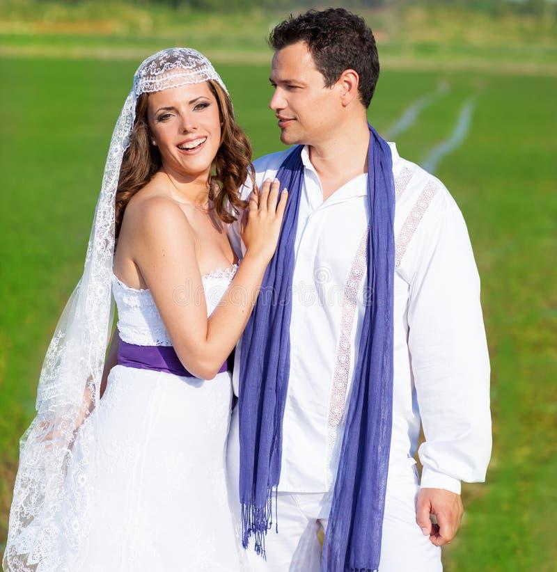 Ζεύγος στο αγκάλιασμα ημέρας γάμου στο πράσινο λιβάδι στοκ εικόνα