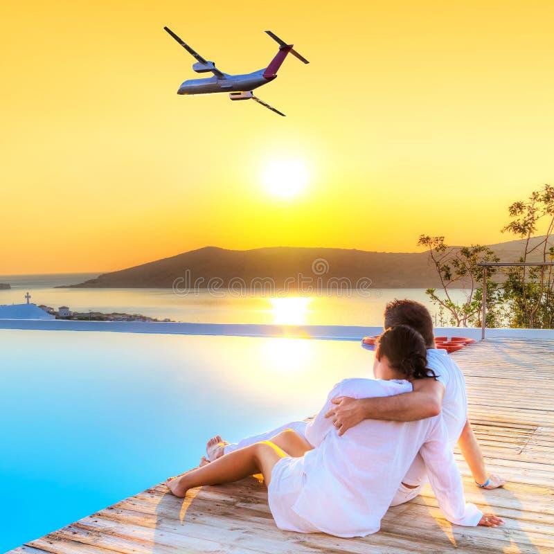 Ζεύγος στο αεροπλάνο προσοχής αγκαλιάσματος στο ηλιοβασίλεμα στοκ φωτογραφία