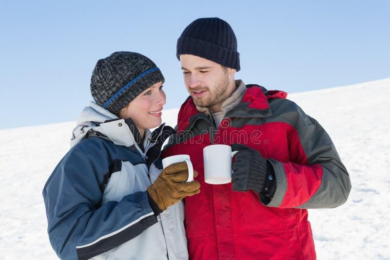Ζεύγος στο θερμό ιματισμό με τα φλυτζάνια καφέ στο χιόνι στοκ εικόνες