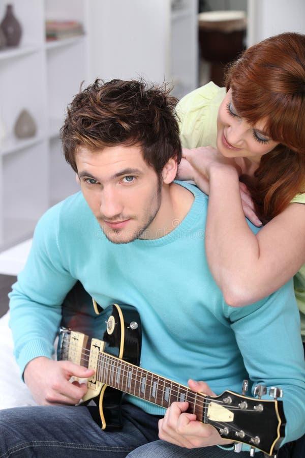 Ζεύγος στο σπίτι με μια κιθάρα στοκ φωτογραφία