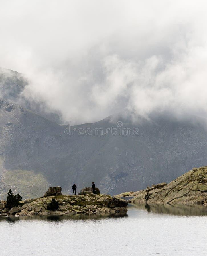 Ζεύγος της στάσης οδοιπόρων κοντά στη λίμνη στοκ εικόνες