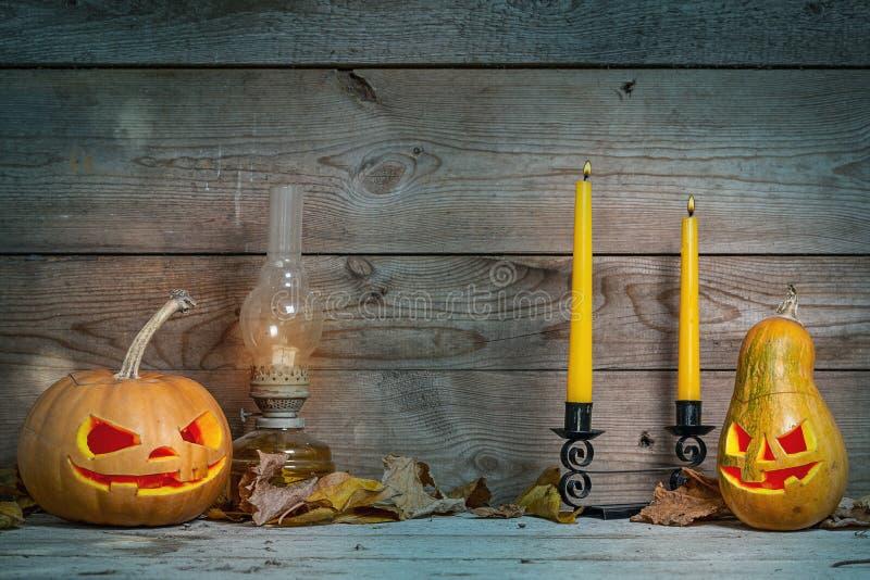 Ζεύγος των διακοσμημένων κολοκυθών για αποκριές σε ένα μυστικό υπόβαθρο φθινοπώρου με τα κεριά και το λαμπτήρα αερίου στοκ φωτογραφία με δικαίωμα ελεύθερης χρήσης