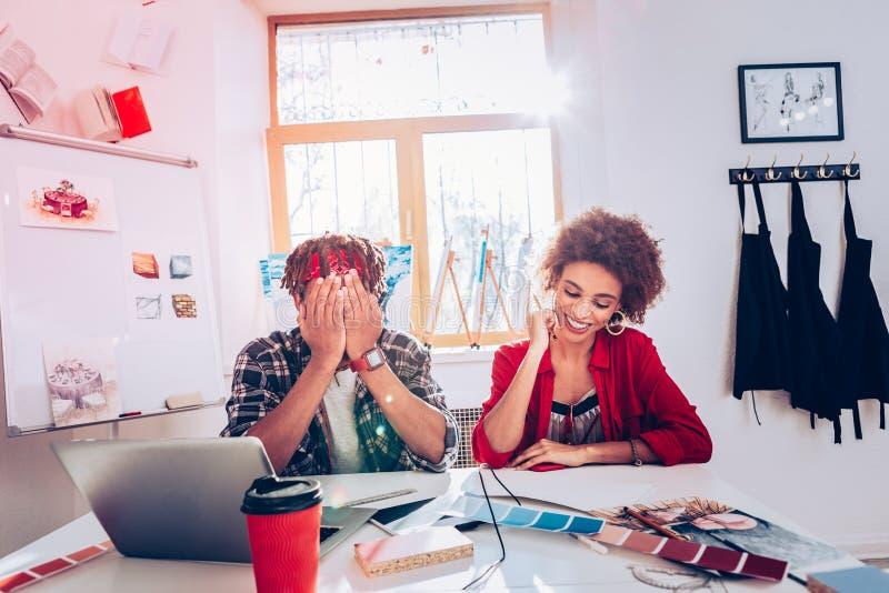 Ζεύγος των εσωτερικών σχεδιαστών που γελούν απολαμβάνοντας τη διαδικασία της εργασίας στοκ φωτογραφίες