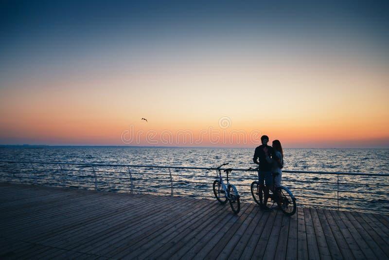 Ζεύγος των νέων εραστών hipster που αγκαλιάζουν στην παραλία και που προσέχουν την ανατολή στον ξύλινο θερινό χρόνο γεφυρών στοκ εικόνες με δικαίωμα ελεύθερης χρήσης