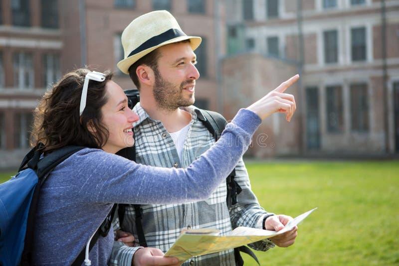 Ζεύγος των νέων ελκυστικών τουριστών που προσέχουν το χάρτη στοκ εικόνες