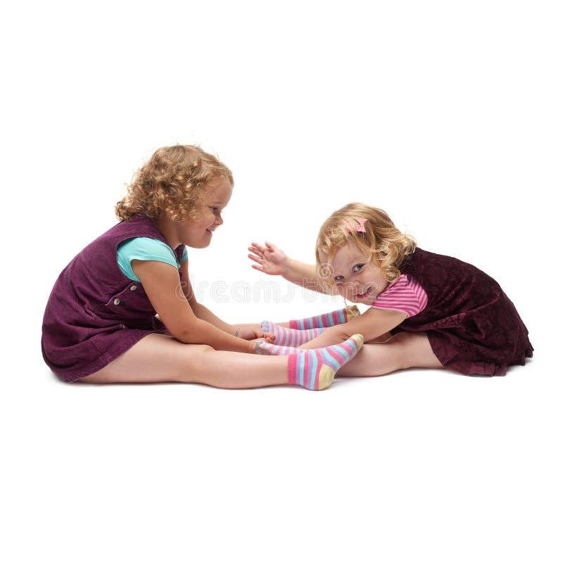 Ζεύγος των νέων μικρών κοριτσιών που κάθονται πέρα από το απομονωμένο άσπρο υπόβαθρο στοκ εικόνες