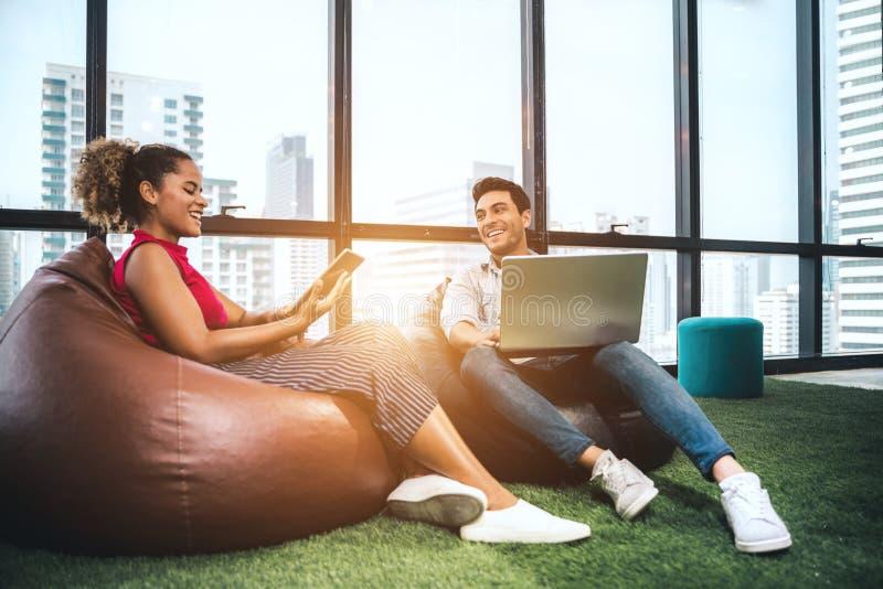 Ζεύγος των νέων σχεδιαστών που εργάζονται στο σύγχρονο γραφείο, δύο συνάδελφοι που συζητά το πρόγραμμα διασκέδασης πέρα από ένα l στοκ εικόνα