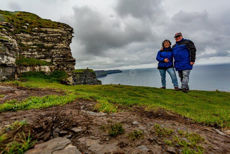 Ζεύγος των ταξιδιωτών με τις μπλε ζακέτες στους απότομους βράχους Moher στοκ φωτογραφία