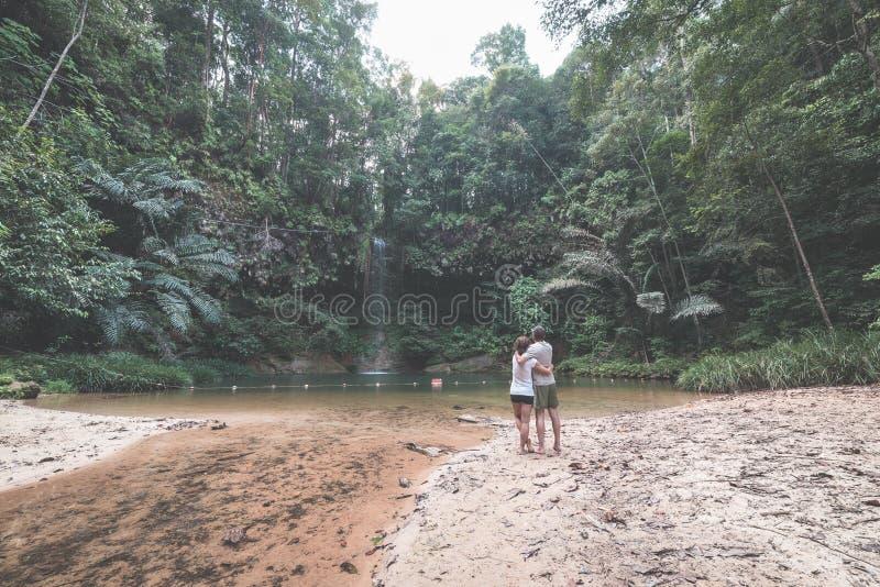 Ζεύγος των τουριστών που εξετάζουν μια ζαλίζοντας πολύχρωμους φυσικούς λίμνη και έναν καταρράκτη στο τροπικό δάσος του εθνικού πά στοκ εικόνες με δικαίωμα ελεύθερης χρήσης