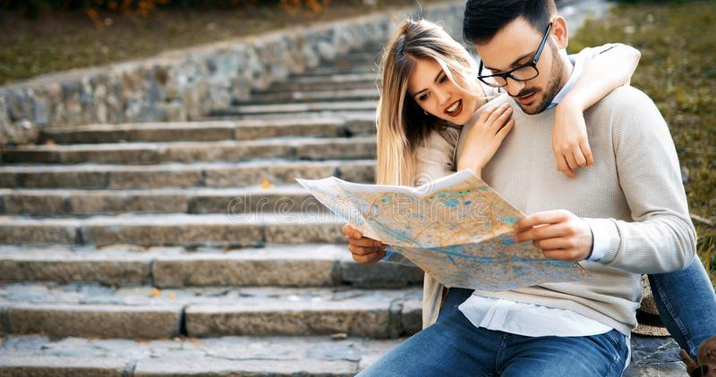 Ζεύγος των τουριστών που εξετάζουν το χάρτη γύρου πόλεων στοκ εικόνα