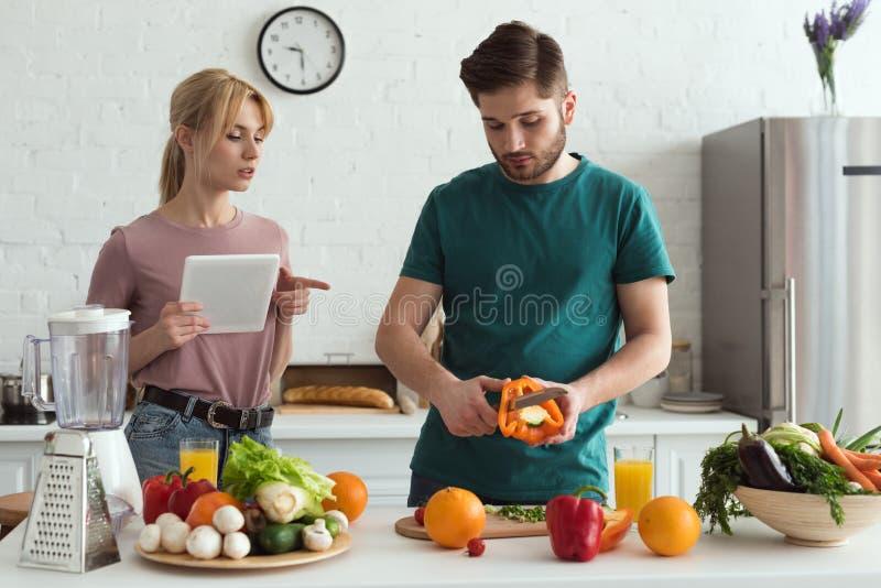 ζεύγος των χορτοφάγων που χρησιμοποιούν την ταμπλέτα με τη συνταγή για το μαγείρεμα στοκ φωτογραφίες