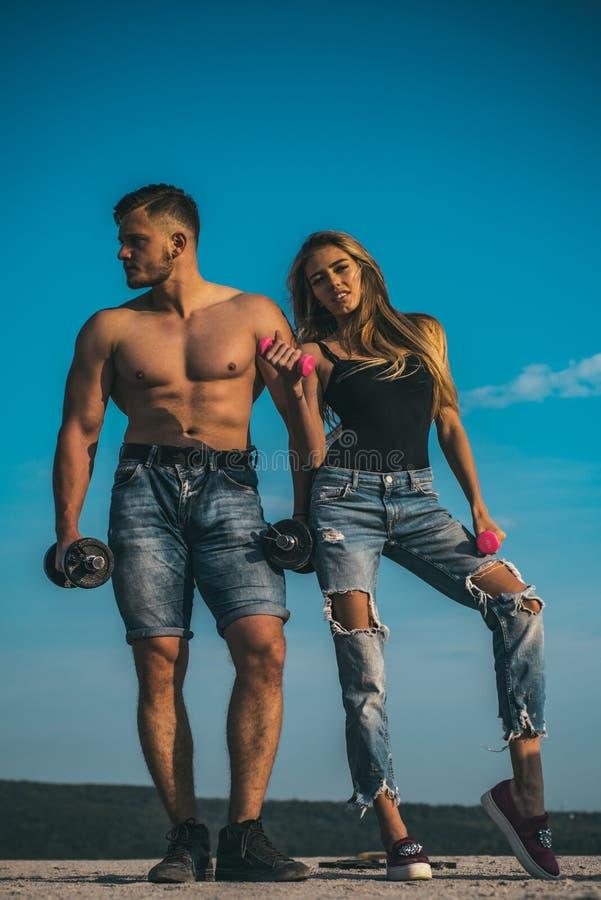 Ζεύγος των bodybuilders που αντλεί επάνω τους μυς με τους αλτήρες , αθλητική έννοια Άτομο με το μυϊκό κορμό στα σορτς τζιν και στοκ φωτογραφία