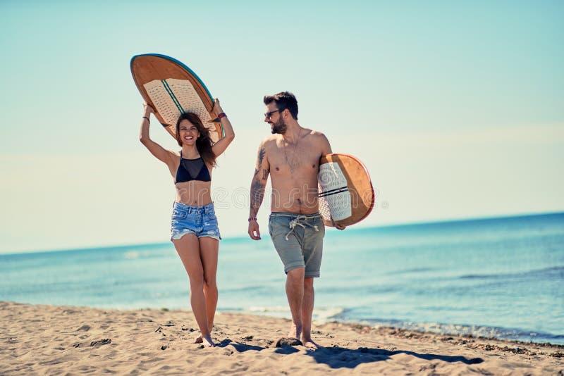 Ζεύγος των surfers που περπατά στις διακοπές παραλιών ακραίος αθλητισμός στοκ εικόνα