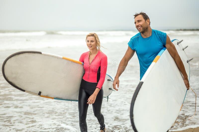 Ζεύγος των surfers στην ωκεάνια ακτή ` s στοκ φωτογραφία