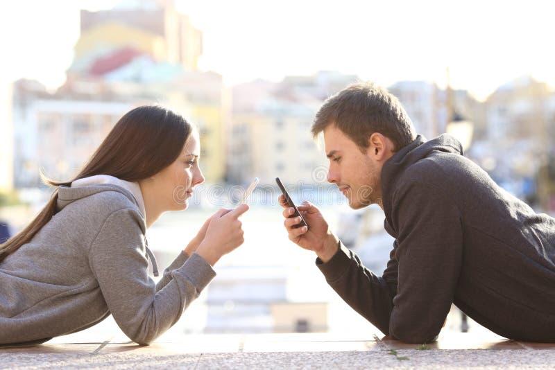 Ζεύγος των teens που βασανίζεται με τα έξυπνα τηλέφωνα στοκ εικόνες