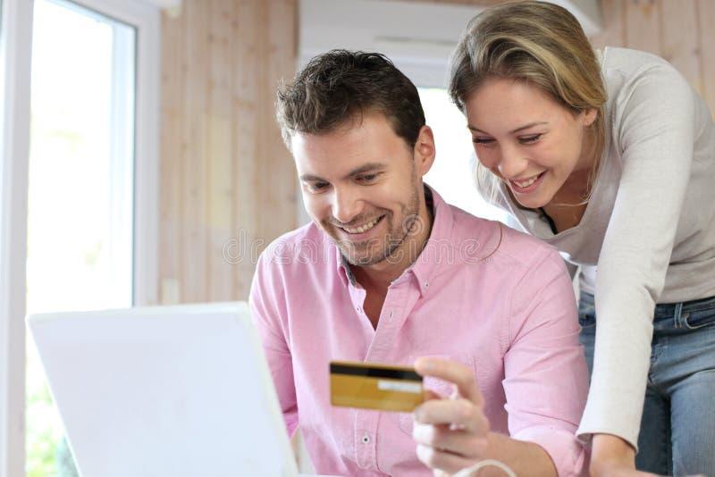 Ζεύγος χρησιμοποιώντας την πιστωτική κάρτα και ψωνίζοντας on-line στοκ εικόνες με δικαίωμα ελεύθερης χρήσης