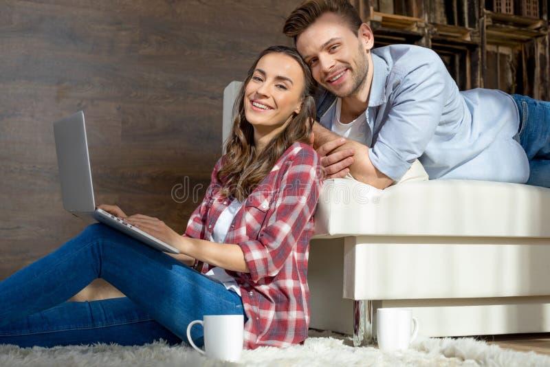 Ζεύγος χρησιμοποιώντας το lap-top στο σπίτι και χαμογελώντας στη κάμερα στοκ φωτογραφία με δικαίωμα ελεύθερης χρήσης