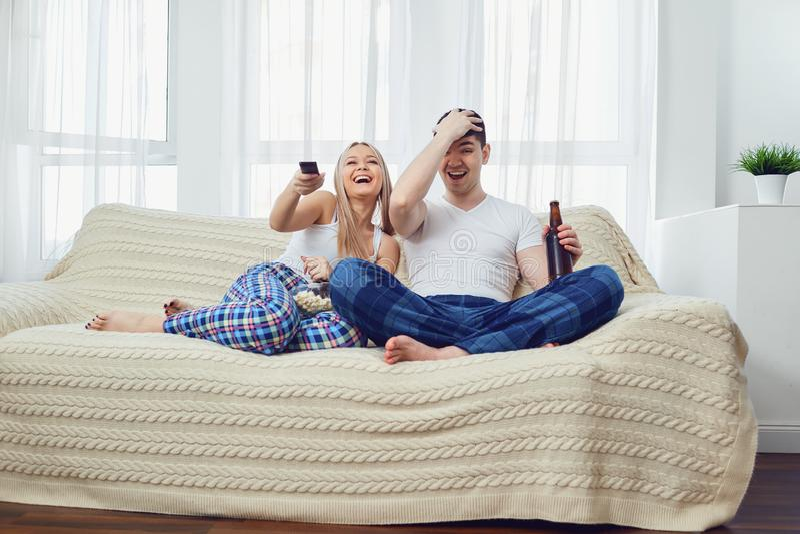 Ζεύγος funs με τη συνεδρίαση TV ρολογιών μπουκαλιών στον καναπέ στο δωμάτιο στοκ φωτογραφία με δικαίωμα ελεύθερης χρήσης