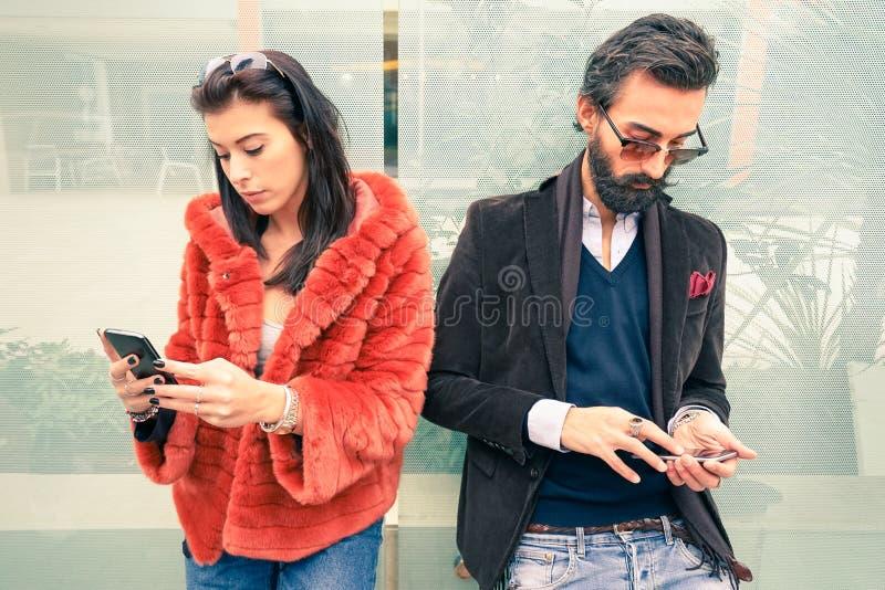 Ζεύγος Hipster στη λυπημένη στιγμή που αγνοεί η μια την άλλη που χρησιμοποιεί το smartphone στοκ εικόνες