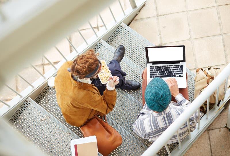Ζεύγος Hipster χρησιμοποιώντας τον υπολογιστή και τρώγοντας το μεσημεριανό γεύμα υπαίθρια στοκ εικόνες