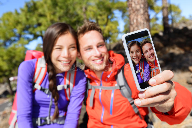 Ζεύγος Selfie που χρησιμοποιεί την έξυπνη πεζοπορία τηλεφωνικών καμερών στοκ φωτογραφία με δικαίωμα ελεύθερης χρήσης