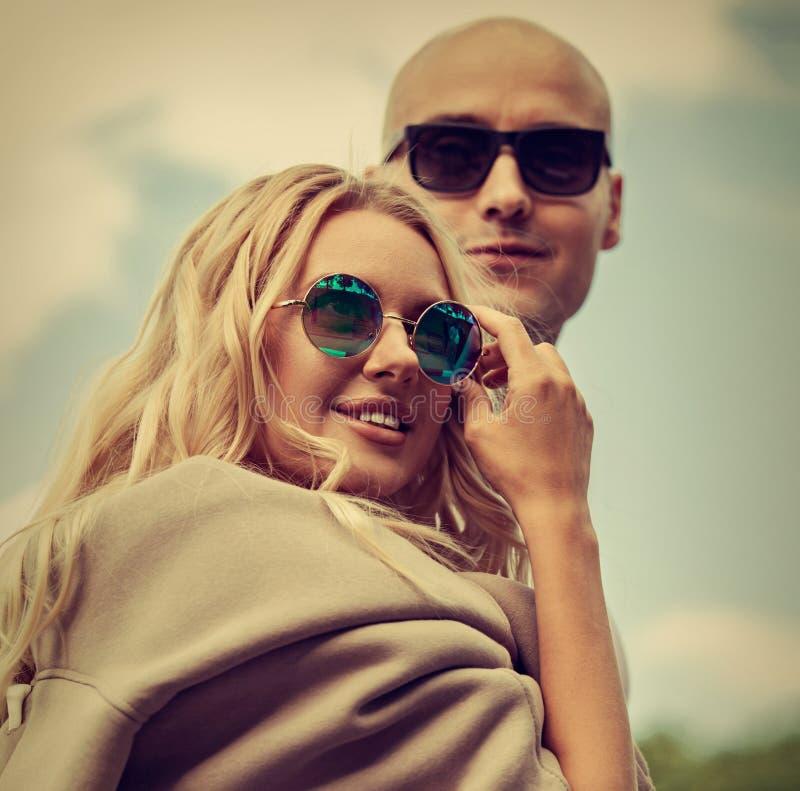 Ζεύγος Stilish που περπατά στα σύγχρονα φορέματα και τα καθιερώνοντα τη μόδα γυαλιά ηλίου στο θερινό υπόβαθρο Όμορφο θηλυκό ξανθό στοκ φωτογραφία με δικαίωμα ελεύθερης χρήσης