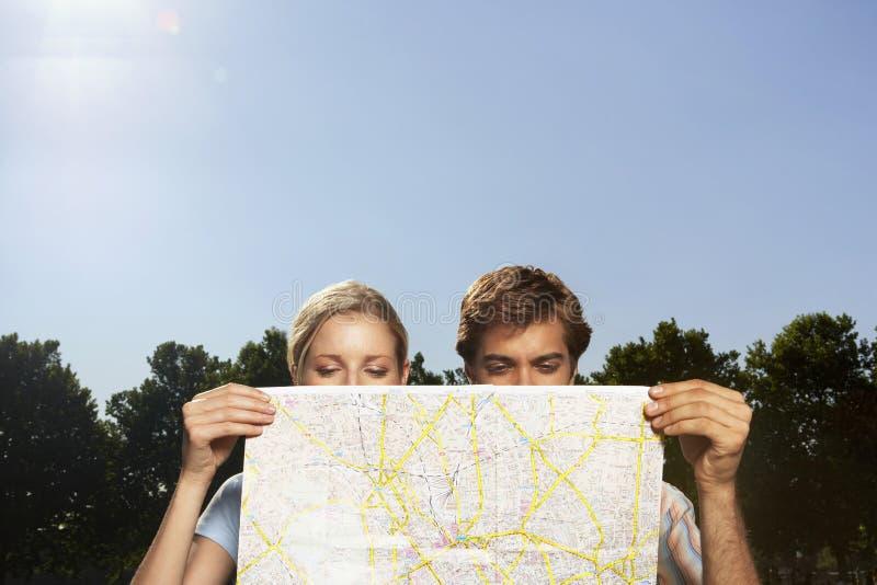 Ζεύγος Vacationing που φαίνεται συνολικά χάρτης στοκ φωτογραφία