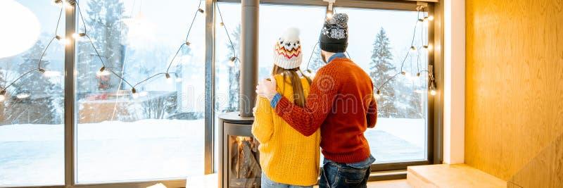 Ζεύγους μαζί στο σύγχρονο σπίτι στα βουνά κατά τη διάρκεια του χειμώνα στοκ εικόνες