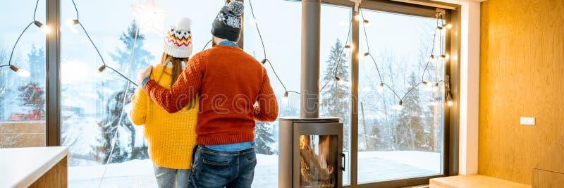 Ζεύγους μαζί στο σύγχρονο σπίτι στα βουνά κατά τη διάρκεια του χειμώνα στοκ φωτογραφία με δικαίωμα ελεύθερης χρήσης