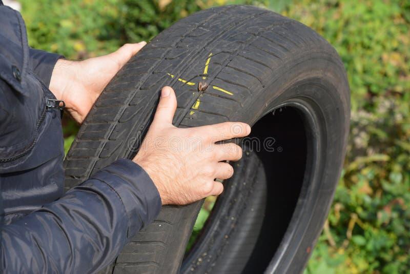 Ζημία ροδών αυτοκινήτων με το καρφί και το κίτρινο σημάδι Επίπεδη ρόδα αυτοκινήτων στα χέρια στοκ φωτογραφία με δικαίωμα ελεύθερης χρήσης