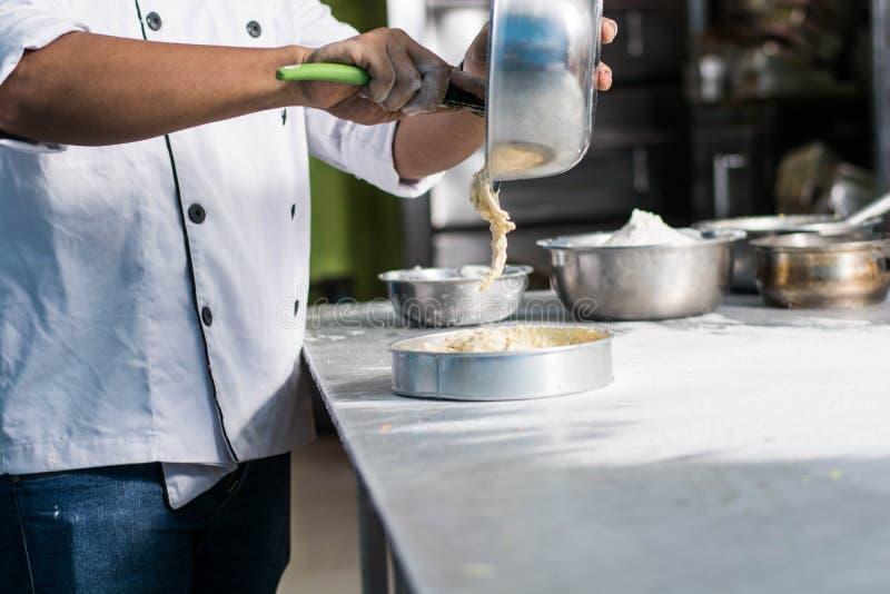 Ζουμ του χύνοντας κτυπήματος χεριών αρχιμαγείρων ζύμης από το κύπελλο χάλυβα στη φόρμα κέικ στον ανοξείδωτο πίνακα μέσα στο ξενοδ στοκ εικόνες
