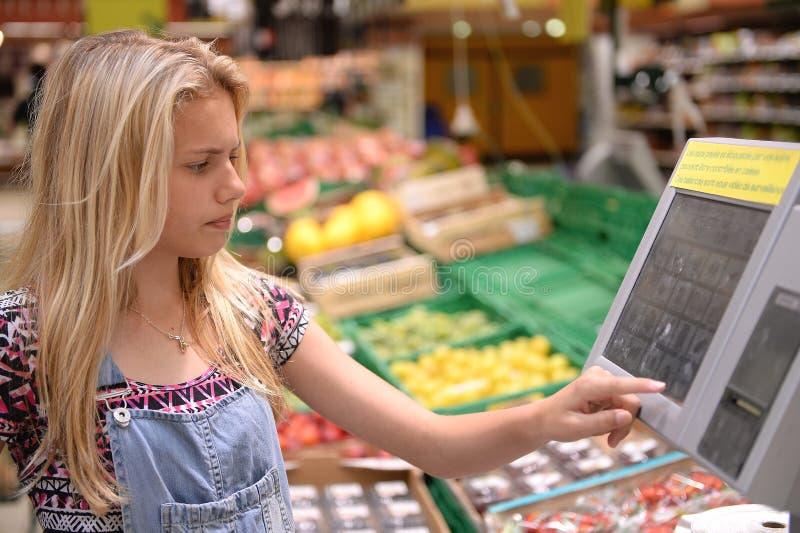 Ζυγίζοντας αγαθά κοριτσιών στο κατάστημα στοκ εικόνες