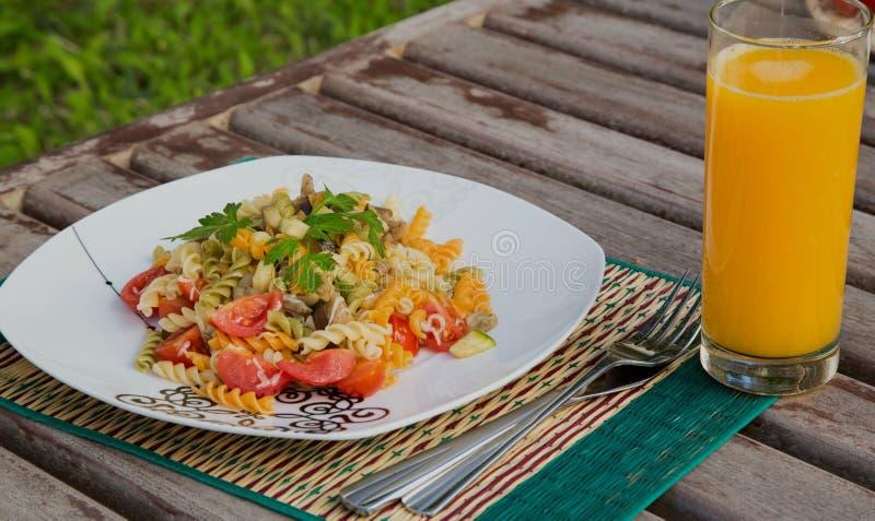 Ζυμαρικά με τα λαχανικά και ένα ποτήρι του φρέσκου χυμού από πορτοκάλι στοκ εικόνα με δικαίωμα ελεύθερης χρήσης