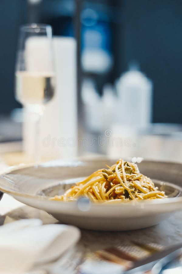 Ζυμαρικά με τα θαλασσινά στο πιάτο με το γυαλί σαμπάνιας στο υπόβαθρο στοκ εικόνα
