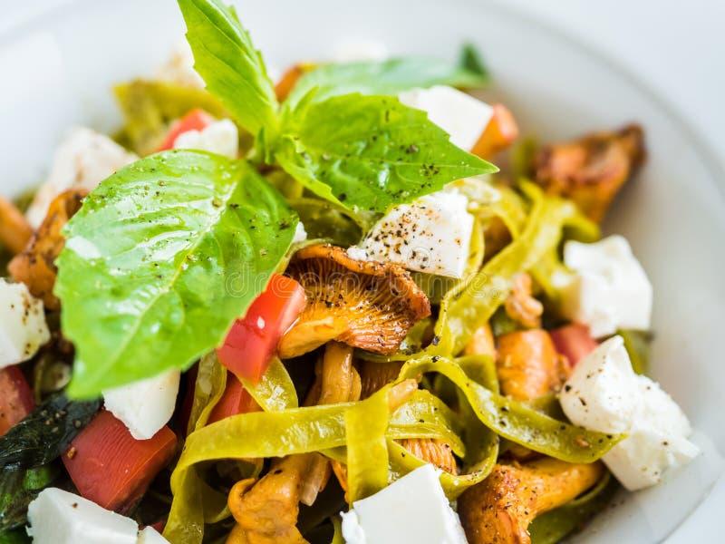 ζυμαρικά με τα πράσινα ζυμαρικά με chanterelle τα μανιτάρια, το τυρί φέτας και το πιπέρι στοκ φωτογραφία