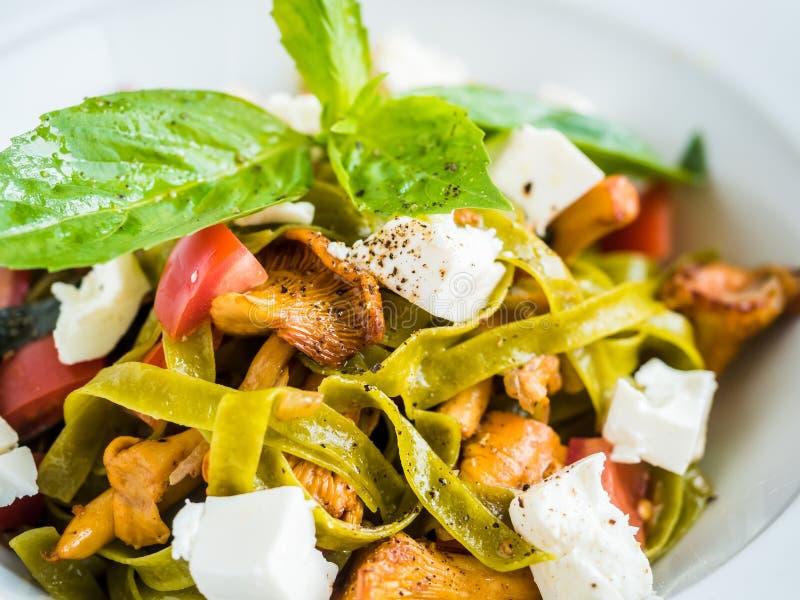 ζυμαρικά με τα πράσινα ζυμαρικά με chanterelle τα μανιτάρια, το τυρί φέτας και το πιπέρι στοκ εικόνες με δικαίωμα ελεύθερης χρήσης