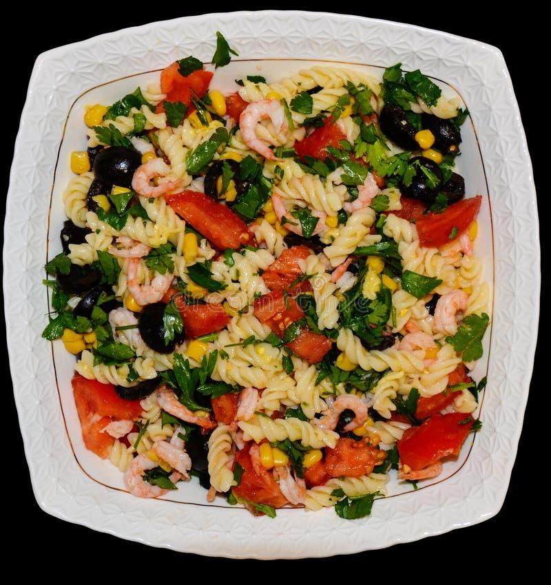 Ζυμαρικά με τη σαλάτα σε ένα άσπρο πιάτο στοκ φωτογραφία