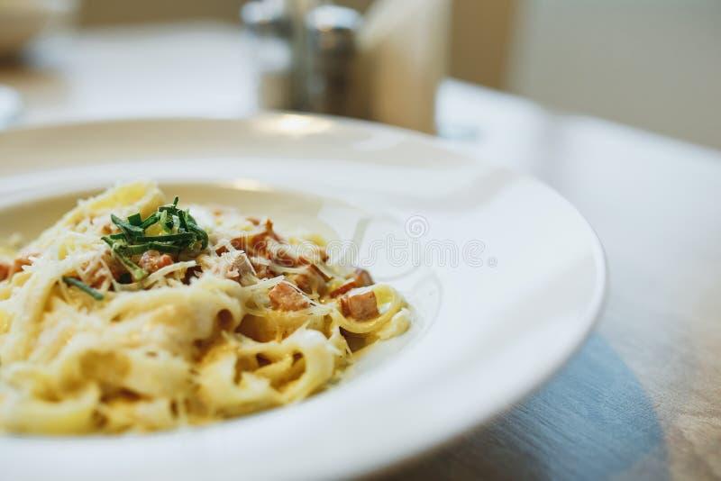 Ζυμαρικά με το κοτόπουλο και ντομάτες με τα φύλλα μαρουλιού σε ένα άσπρο πιάτο κλείστε επάνω στοκ εικόνες