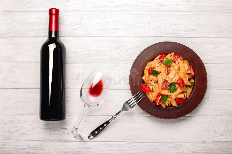 Ζυμαρικά με το τυρί, την ντομάτα κερασιών, wineglass και το κρασί μπουκαλιών στους λευκούς ξύλινους πίνακες στοκ φωτογραφία