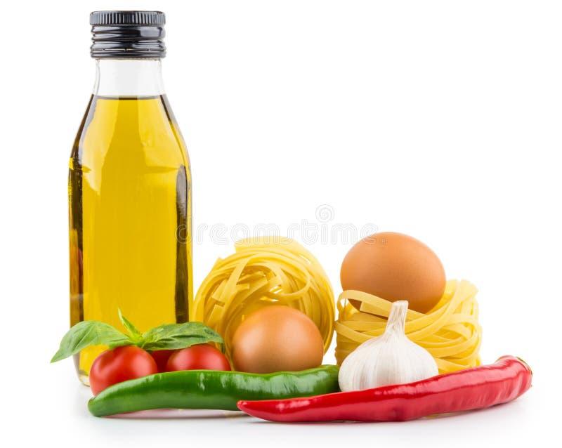 Ζυμαρικά, μπουκάλι του ελαιολάδου, ντομάτες, σκόρδο, πιπέρι και βασιλικός στοκ εικόνες με δικαίωμα ελεύθερης χρήσης