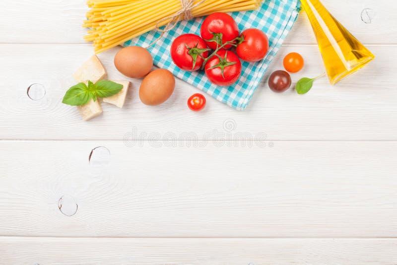 Ζυμαρικά, ντομάτες, βασιλικός στον ξύλινο πίνακα στοκ εικόνες με δικαίωμα ελεύθερης χρήσης