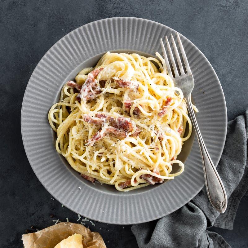 Ζυμαρικά Carbonara, μακαρόνια με το pancetta, αυγό, σκληρές τυρί παρμεζάνας και σάλτσα κρέμας alla μελιτζανών ανασκόπησης παραδοσ στοκ εικόνες