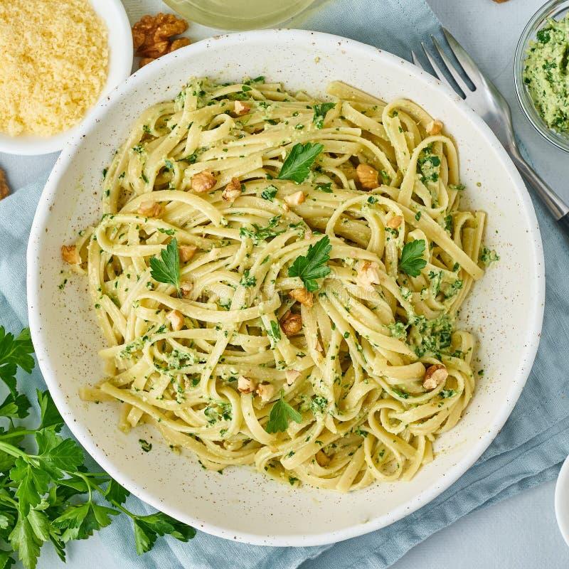 Ζυμαρικά Pesto, bavette με τα ξύλα καρυδιάς, μαϊντανός, σκόρδο, καρύδια, ελαιόλαδο Τοπ άποψη, κινηματογράφηση σε πρώτο πλάνο, μπλ στοκ εικόνα